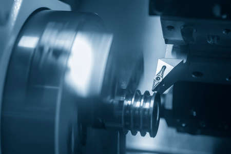 The CNC lathe machine groove cutting the metal pulley parts. The hi-technology metal working processing by CNC turning machine .