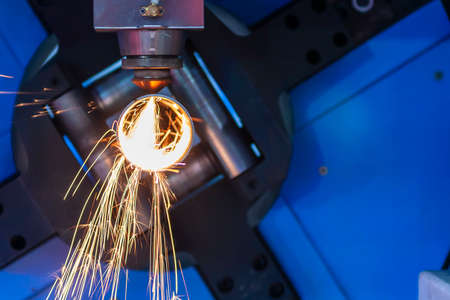 The fiber laser cutting machine cutting the metal pipe .The hi-technology metal working process by laser cutting machine.
