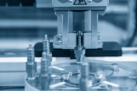 The automatic robotic arm gripping the spark plug part in production line. The hi-technology material handling system with robotic system.