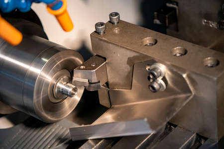 The  CNC lathe machine thread cutting the metal shaft parts. The hi-technology metal working processing by CNC turning machine .