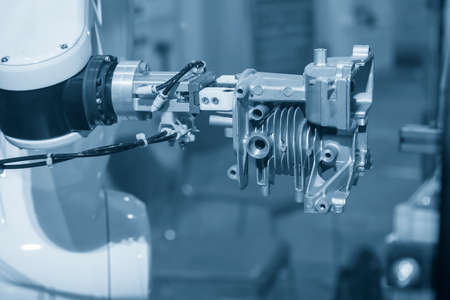 The robotics arm gripping the motorcycle engine parts. The hi-technology  autonomous manufacturing process of automotive parts. 版權商用圖片 - 158150937