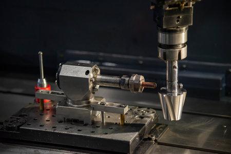The sinker EDM machine operation with mold insert part. The 4-axis EDM machine control by CNC program. 版權商用圖片 - 161783474