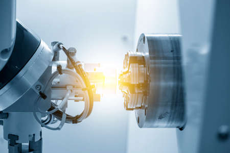 The robotics arm gripping the metal part from CNC lathe machine with lighting effect. The hi-technology  autonomous manufacturing process of automotive parts by turning machine.