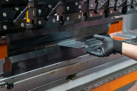 The technician operator working with press brake hydraulic bending machine. The sheet metal working operation by skill operator.