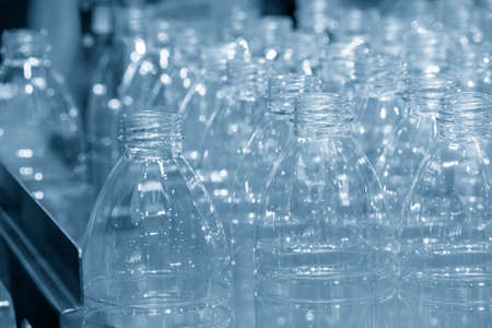 The PET bottles  on the conveyor belt for filling process in the drinking water factory. The hi-technology of plastic bottle manufacturing process.