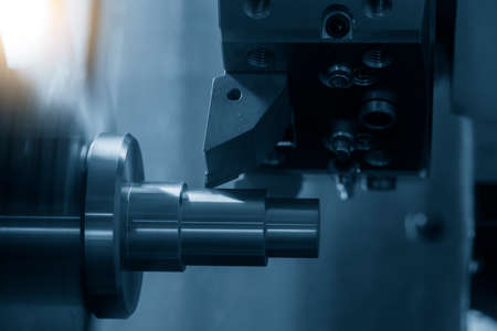 The CNC lathe machine cutting the metal cone shape parts. The hi-technology metal working processing by CNC turning machine . Imagens