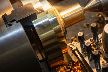 The operation of lathe machine cutting the brass shaft material. The metalworking process by turning machine. Stock Photo