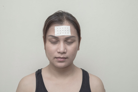 head pain: Women head pain and sticking plaster. Stock Photo