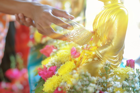 Watering Buddha at the Water Festival In bright orange light. Stock Photo