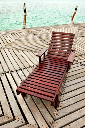 Wooden Chaise Longue On The Dock Stock Photo