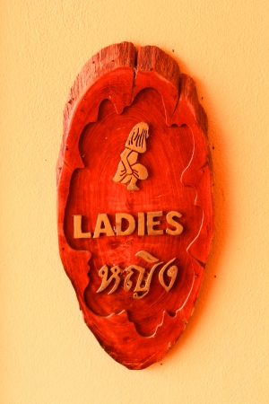 defecate: Woman wooden carving vintage sign in Thai language