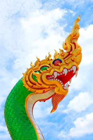 Golden head dragon with a green body statue at Thai Buddhist temple