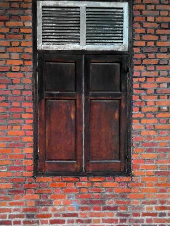 Wooden window on orange brick wall photo