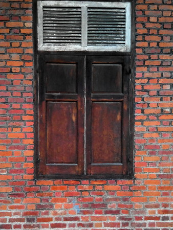 Wooden window on orange brick wall Stock Photo