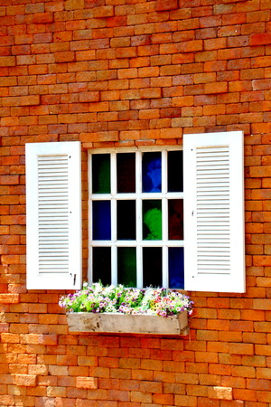 decorration: White wooden window on brick wall with flowers
