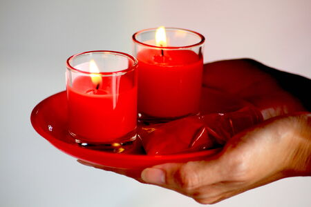 Twain red candle in glasses above your hand Stock Photo