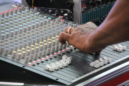 sound mixer: Hand on a sound mixer, operating the leader
