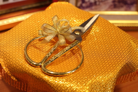 messaline: Scissors tied with ribbon on gold satin Stock Photo