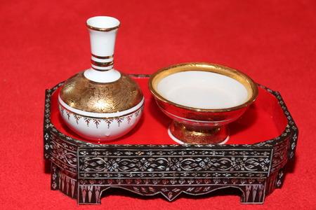 marqueteria: Porcelana verter agua en la bandeja ceremonial de marquetería sobre fondo rojo Foto de archivo