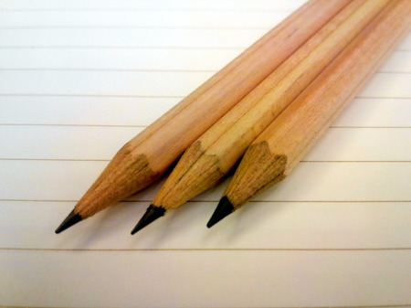 describe: Three wooden pencil on white paper