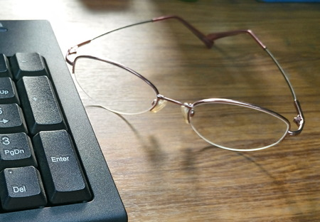 resound: Sunlight reflex with eyeglasses and keyboard on wood table