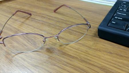 Eyeglasses with keyboard on wood table Stock Photo