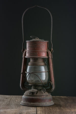 Old oil lamp on dark background.