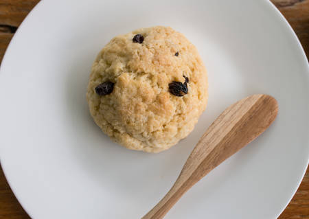 peice: peice of blueberry scone on white plate and wodden spoon Stock Photo
