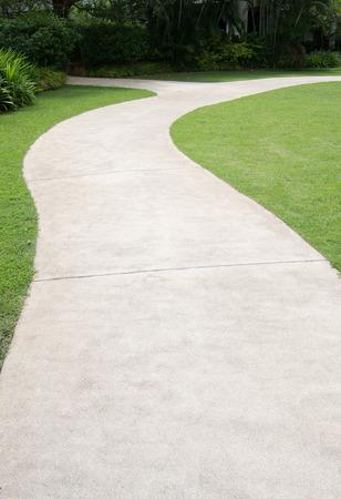 garden path: Path way across green grass in beautiful tropical garden. Stock Photo