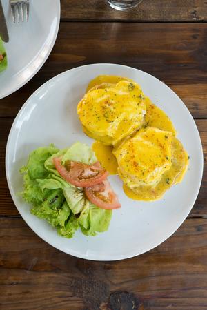 Eggs Benedict with salad top view