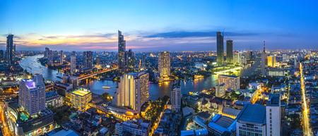 Curva do rio e da opinião lateral do rio bonito. Em uma zona comercial principal de Bangkok. Combina um contraste de edifícios brilhantes e casas negras. Com um céu colorido do sol