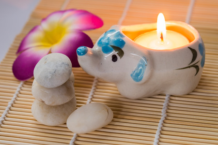 Elephant Candle and white stones with flower on bamboo mat photo