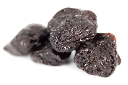 prunes: Close up group of prunes on white background
