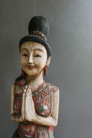 thai style: Thai style wooden woman statue doing Sawasdee