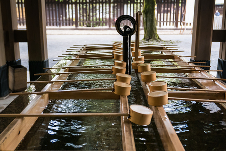 observers: Tokyo, Japan - November 30, 2015: A purification trough by the entrance to the Meiji Shrine in Tokyo. Shinto observers use it to wash their hands and mouths before entering the shrine.