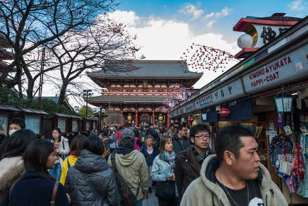 crowded space: Tokyo, Japan - Nov 30, 2015: Crowds of visitors browsing the colourful market stalls of Nakamise-dori the popular destination leading to Senso-ji temple in the Asakusa district of downtown Tokyo, Japan. Crowds of visitors browsing the colourful market st