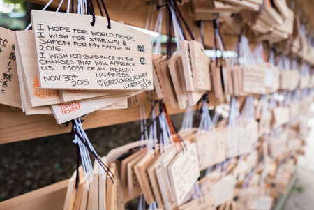 ema: Tokyo, Japan - November 30, 2015: People write their wish on a wooden board (ema) and leave that at the Meiji Shrine, a Shinto complex in Tokyo dedicated to the Emperor Meiji and his wife, Empress Shōken. Completed in 1926, it is situated in 175 acres of