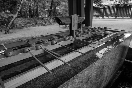 observers: Tokyo, Japan - November 30, 2015: Black and white photo of A purification trough by the entrance to the Meiji Shrine in Tokyo. Shinto observers use it to wash their hands and mouths before entering the shrine. Editorial