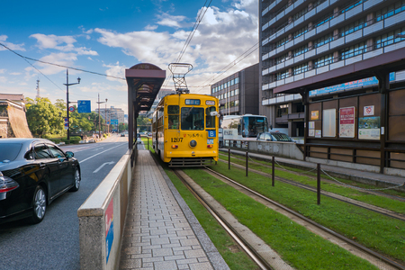 local 27: KUMAMOTO, JAPAN - SEPTEMBER 27, 2014: Classic tram of Kumamoto city at the tram stop near Kumamoto castle in Kumamoto, Kyushu , Japan. Team is the easiest way to access tourist spot in Kumamoto city is by using local trams service. Editorial