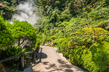 garden features: Garden in Umi Jigoku or Sea hell in Beppu, Oita, Japan is one of the most beautiful hells, the sea hell features a pond of boiling, blue water. In its spacious gardens, there are a few secondary, orange colored hells and a large, clear water pond with l Stock Photo