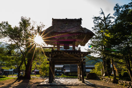 Shirakawa-go, Japan - May 2, 2016: Bell tower with sun flare at the temple in Shirakawa-go. Shirakawa-go is one of Japans UNESCO World Heritage Sites located in Gifu Prefecture, Japan.