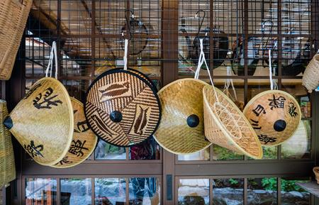 gassho zukuri: Shirakawa-go, Japan - May 3, 2016: Wide-brimmed rain hat selling in souvenirs shop in Shirakawa-go. Shirakawa-go is one of Japans UNESCO World Heritage Sites located in Gifu Prefecture, Japan.