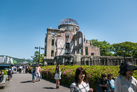 Hiroshima, Japan - May 5, 2016: Tourists at Atomic Bomb Dome. Atomic Bomb Dome or Genbaku Domu (A-Bomb Dome) in Hiroshima, Japan is part of the Hiroshima Peace Memorial Park and was designated a UNESCO World Heritage Site in 1996.