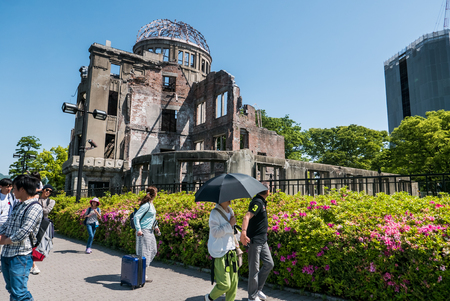 world war ii: Hiroshima, Japan - May 5, 2016: Tourists at Atomic Bomb Dome. Atomic Bomb Dome or Genbaku Domu (A-Bomb Dome) in Hiroshima, Japan is part of the Hiroshima Peace Memorial Park and was designated a UNESCO World Heritage Site in 1996.
