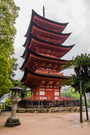storied: Miyajima, Japan - May 6, 2016: Five-storied Pagoda (Gojunoto) on Miyajima Island.  Miyajima island is a famous island shrine-town is a UNESCO World Heritage Site and a major tourism destination.