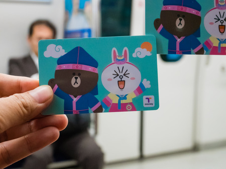 Seoul, South Korea - October 16, 2017: Hand holding T-Money card with Line characters in Subway at Incheon International Airport in  Seoul, South Korea. Sajtókép