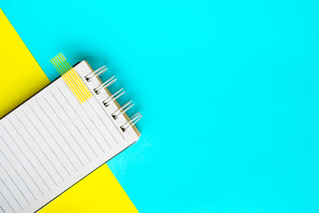 Notebook on Blue and yellow paper background