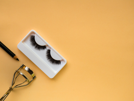 False Eyelashes, eyelash curler and eye liner on yellow background