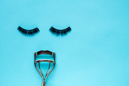 False Eyelashes and eyelash curler on blue background Reklamní fotografie