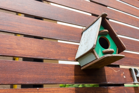 Colorful birdhouse on wooden fence Stock Photo